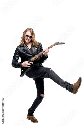 Valokuva  handsome rocker in sunglasses posing playing electric guitar isolated on white,