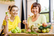 Young and older women sitting with healthy food and fresh drinks after the sports training indoors on the window background