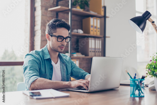 Young handsome minded man in jeans shirt and spectacles sitting at the table and typink a letter to his acquaintance