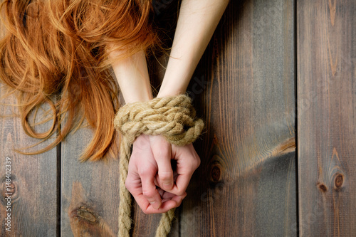 Photo redhead skinny woman bounded with rope, hands close-up