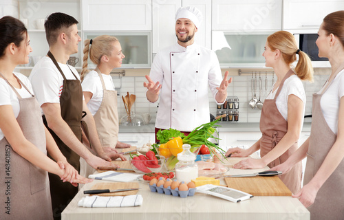Photo sur Aluminium Cuisine Male chef and group of people at cooking classes