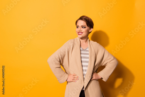 Fotografía  Stylish young beautiful girl in fashionable  beige cardigan is standing on bright yellow background