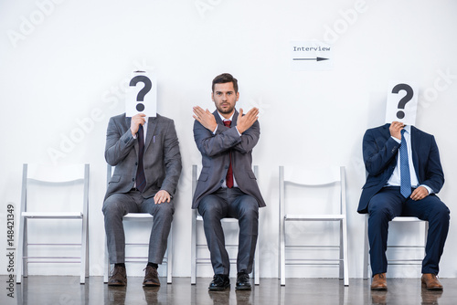 Photo  businesspeople sitting in queue and waiting for interview, holding question mark