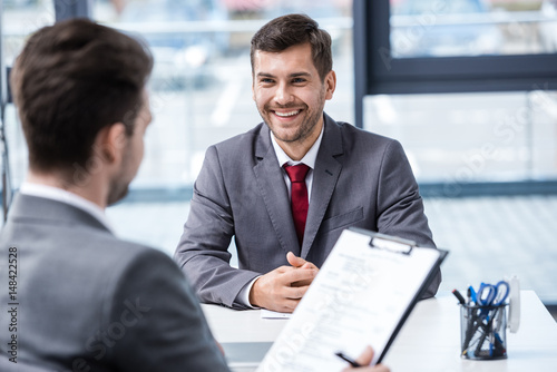 Smiling young businessman looking at manager with clipboard at job interview, business concept