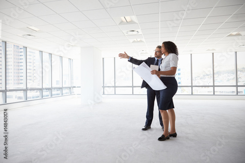 Fotografie, Obraz  Businesspeople Meeting To Look At Plans In Empty Office