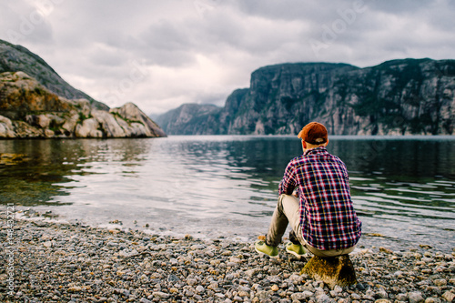Plakat  Lonely traveler tourist man resting on shore of fjord in Norway with  far view of water and mountains valley at horizon in summer cloudy day