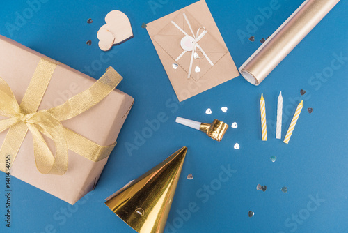 Top View Of Gift Box Candles Birthday Hat And Envelope Isolated On Blue Party Concept