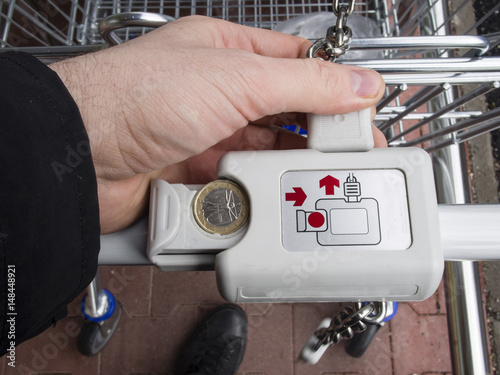 Locking and unlocking the supermarket trolley with one euro coin for grocery shopping,