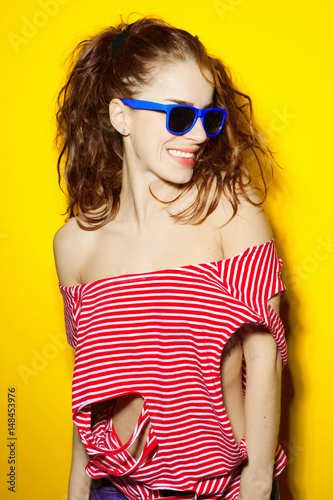 0755c0ccd Beautiful young sexy girl in blue sunglasses and a red striped T-shirt  laughing and