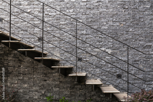 Photo Stands Stairs Marble stairs with metal handrail on granite wall