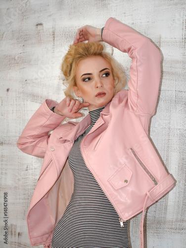 Spoed Foto op Canvas Bar Молодая красивая девушка блондинка позирует в розовой весенней осенней куртке