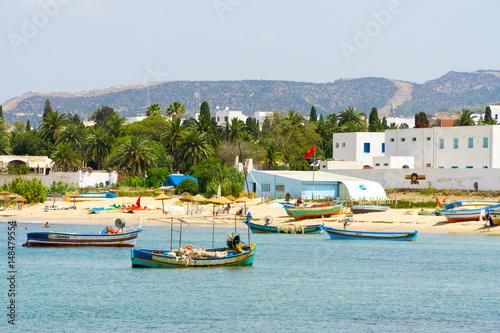 Poster de jardin Tunisie Blick auf den Strand und das Meer bei Hammamet mit Fischerbooten im Wasser.