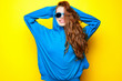Leinwandbild Motiv Beautiful young sexy girl in blue blouse and sunglasses having fun and laughing on a yellow background