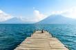 Man sitting on Pier at San Marcos La Laguna with beaufiful scenery of Lake Atitlan and volcanos - Guatemala
