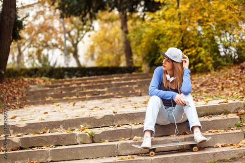 Plakat Portret młoda kobieta z deskorolka obsiadaniem w parku.
