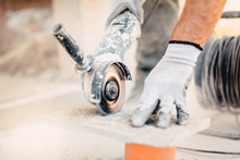 Close-up Of Worker Cutting Stone With Grinder. Dust While Grinding Stone Pavement