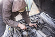 Working man with dirty hands and tools checking car engines