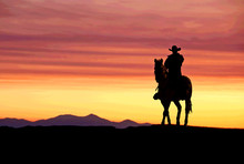Cowboy On Horse At Sunset In The American West