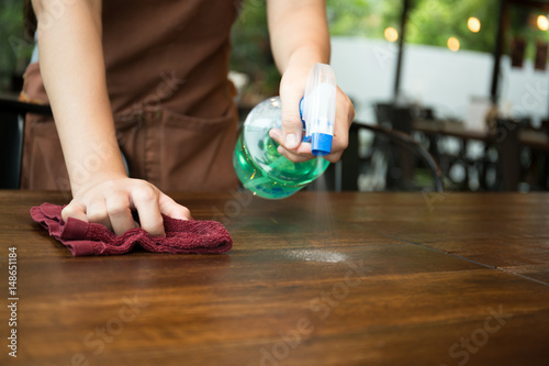 Fotografía  Waitress cleaning the table with spray disinfectant