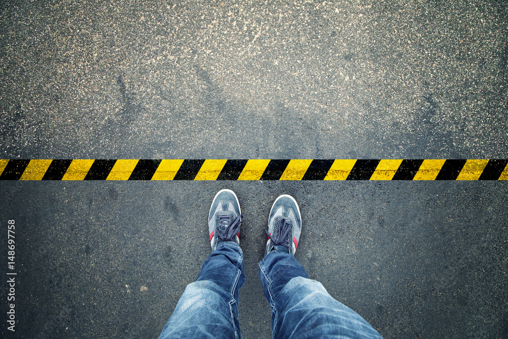Fototapeta Top view of a man stands on industrial striped asphalt floor with warning yellow black pattern.