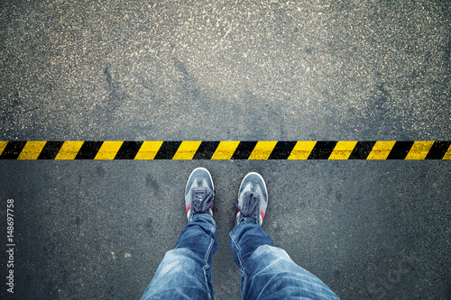 Fototapeta Top view of a man stands on industrial striped asphalt floor with warning yellow black pattern. obraz