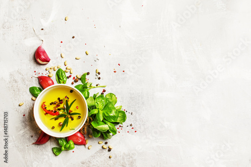 Photo sur Toile Condiment Food background, olive oil, cedar nuts, spices and herbs, green basil and garlic, flat lay