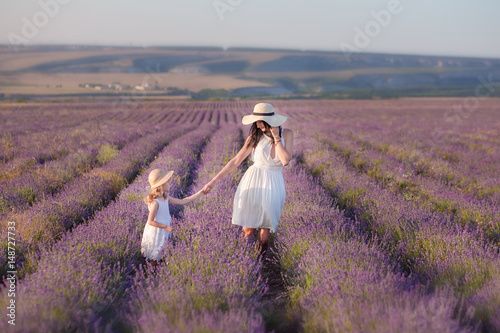 Photo  Young beautiful lady mother with lovely daughter walking on the lavender field on a weekend day in wonderful dresses and hats