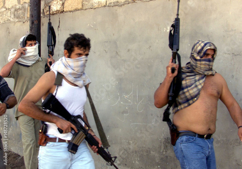 Palestinians carry guns during clashes with Israeli soldiers