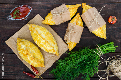Foto Traditional national English (Cornish) meat patties (pie) - Cornish pasty on a dark wooden table