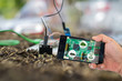 canvas print picture - Agricultural technology and organic agriculture concept. Smart farmer holding smart phone with agritech icons and messages on screen with soil sensor to manage water, soil quality and monitor weather.