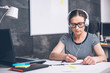 Woman writing notes and listening music at the office