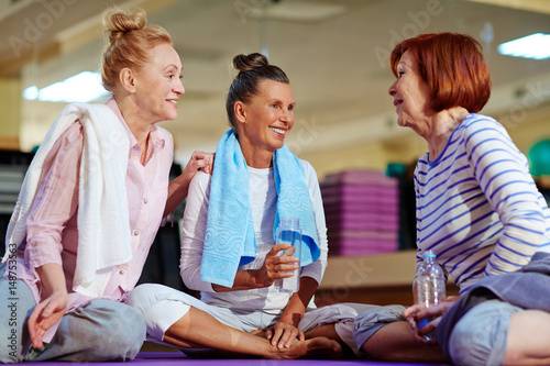 Fotografía  Friendly aged females drinking water and discussing workout at break