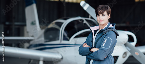 Vászonkép Smiling female pilot posing with her plane