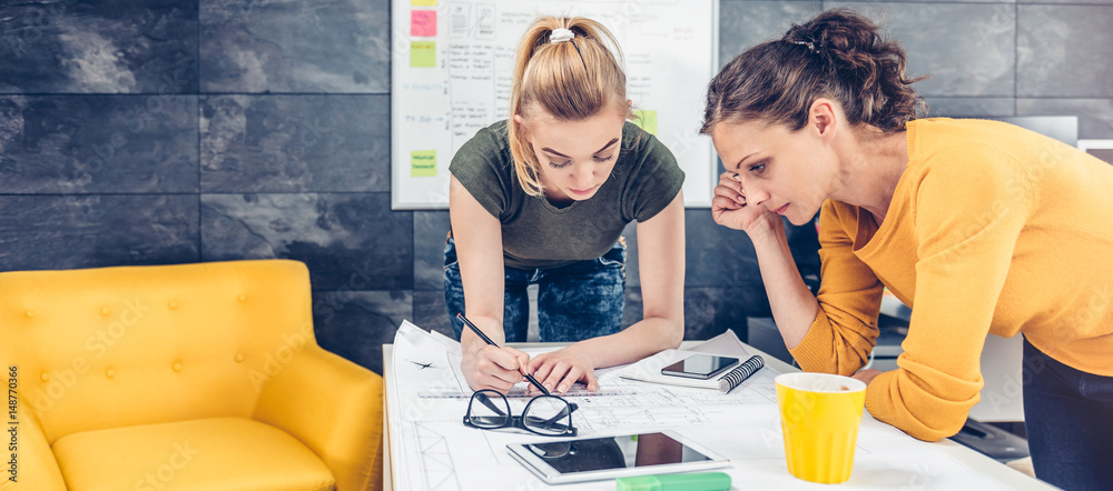 Fototapety, obrazy: Two business woman checking blueprints