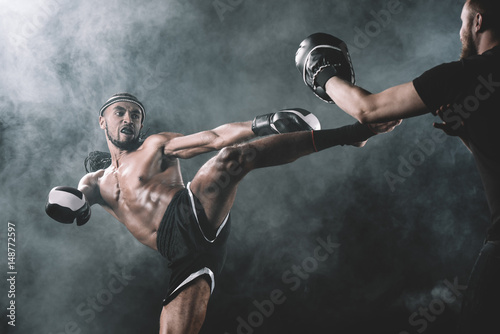 side view of concentrated muay thai fighter practicing kick isolated on black, fight club concept