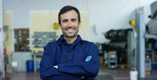Fotografía  Portrait of a young beautiful car mechanic in a car workshop, in the background