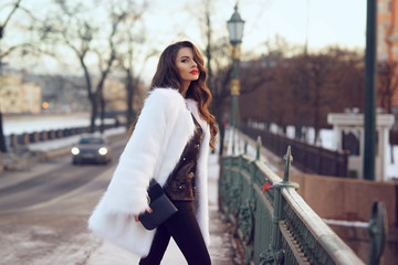 Young beautiful stylish woman walking down the street on a cold winter snowy day. Fashionable girl wearing black blouse and trousers and white fur coat. Female with long curly hair.