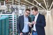 Two men with tablet talking in factory shop floor