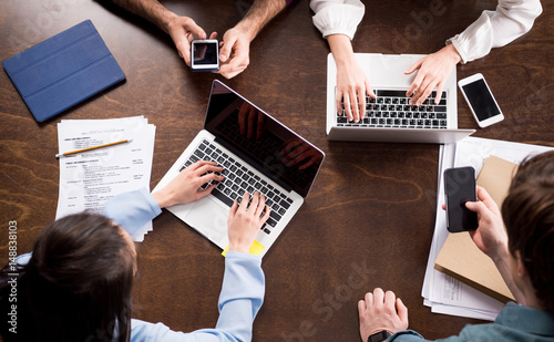 Fotomural  Overhead view of young businesspeople sitting together at workplace and using di