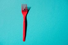 Top View Of Red Plastic Fork Isolated On Blue