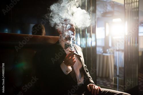Fotografie, Tablou  A brutal man in a dress coat smokes a cigar.
