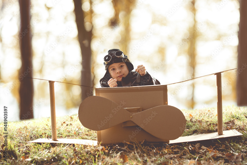 Fototapeta front view vintage pilot boy flight by imagination on cardboard plane outdoor