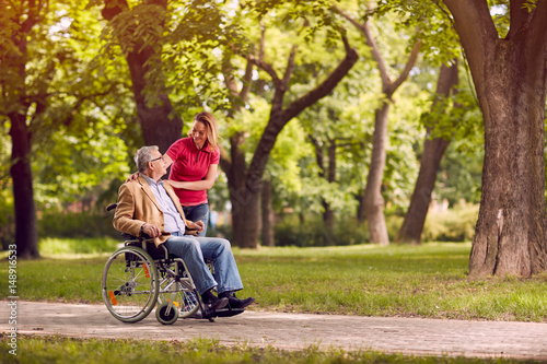 Fotografia  senior man in wheelchair in the park with daughter.