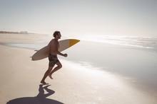 Shirtless Man Running While Holding Surfboard At Beach