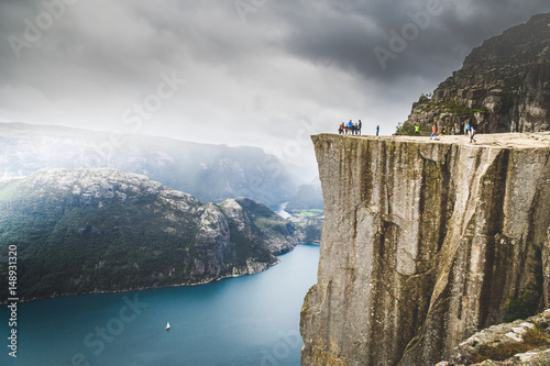 People hiking to Preikestolen, famous nature landmark in Norwey. Lysefjorden and mountains in background.