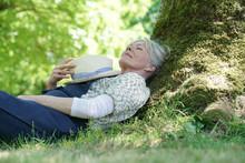Senior Woman Relaxing In Garden By Tree