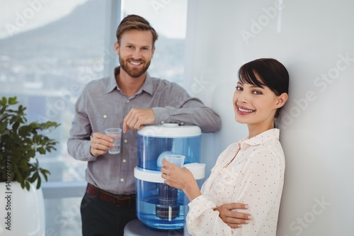 Portrait of smiling executives holding glasses of water