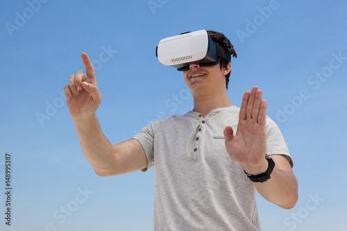 Fotografie, Obraz  Man using vr headset against the blue sky