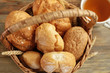 Wicker basket with different fresh bread loaves on table