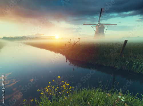 Foto  Landscape with tulips, traditional dutch windmills and houses near the canal in Zaanse Schans, Netherlands, Europe